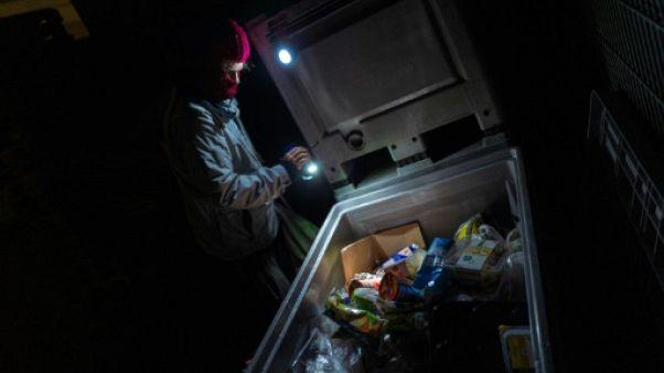 """Un """"cambrioleur de poubelles"""" inspecte celle d'un supermarché pour lutter contre le gaspillage alimentaire, le 17 mai 2019 à Berlin"""