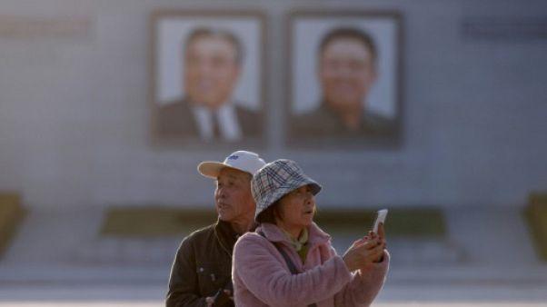 Des touristes chinois prennent des photos sur la place Kim Il Sung à Pyongyang, le 14 avril 2019 en Corée du Nord