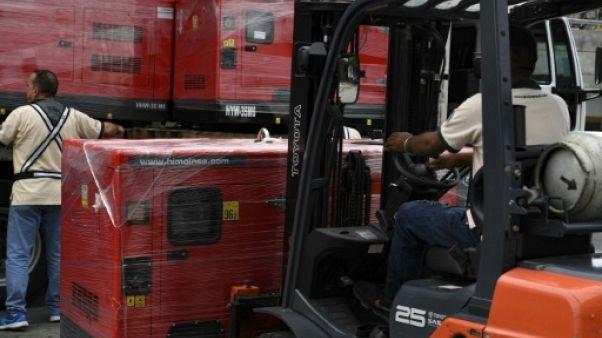 Des employés déchargent des générateurs destinés aux hôpitaux pour les soutenir dans la crise sanitaire, le 17 juin 2019 à Caracas, au Venezuela