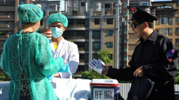 Des membres du mouvemeny spirituel Falun Gong mettent en scène un prélèvement forcé d'organes en Chine pour les vendre, lors d'une manifestation à Taipei, le 20 juillet 2014