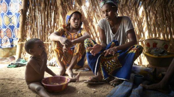 Une mère et ses enfants, de la communauté peule, sous une tente d'un camp de réfugiés installé dans la banlieue de Bamako, le 8 mai 2019