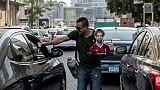 Un vendeur ambulant de café ou de thé, portrait de Mohamed Salah en main, dans les rues du Caire, le 17 juin 2019