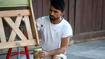 Painting and scraping: An Afghan refugee's hopes for German residence