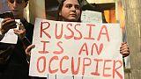 """Une protestataire porte une pancarte avec le slogan """"La Russie est un occupant"""" devant le Parlement géorgien à Tbilissi, le 20 juin 2019"""