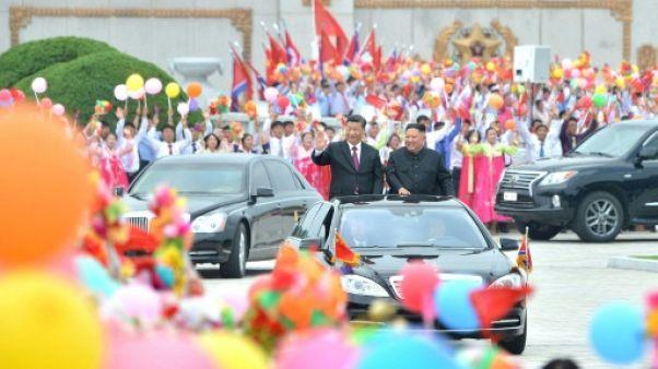 Photo fournie par l'agence nord-coréenne Kcna du dirigeant nord-coréen Kim Jong Un (d) accueillant le président chinois Xi Jinping, le 20 juin 2019 à Pyongyang