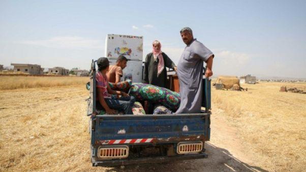 Des déplacés syriens transportent à bord d'un pick-up des affaires pour les vendre dans les environs de la ville d'Abyane, dans la province d'Alep (nord) le 13 juin 2019