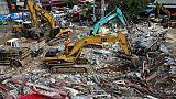 Des secouristes déblaient les décombres d'un immeuble en construction qui s'est effondré à Sihanoukville le 23 juin 2019