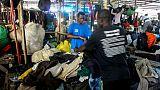 Mamadou Sarr (g), 23 ans, prépare son stand de vêtements d'occasion sur le marché de Colobane, à Dakar, le 25 juin 2019