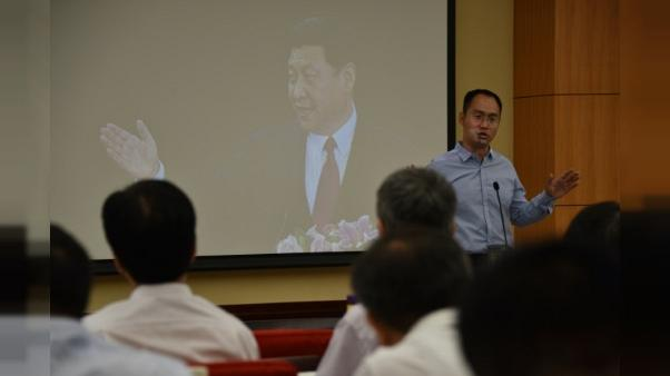 Un enseignant de l'école centrale du parti communiste dans sa classe, où le portrait du président chinois Xi Jinping est projetée, à Pékin le 26 juin 2019