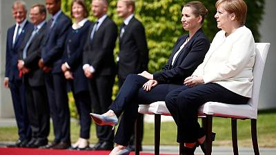 In protocol breach, Merkel sits to welcome Danish PM after shaking bouts