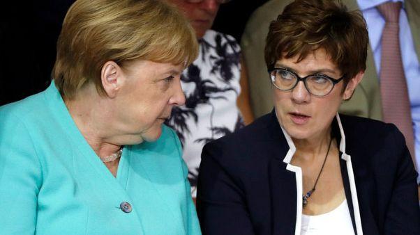 Eyeing power, Merkel protegee starts high-stakes defence job
