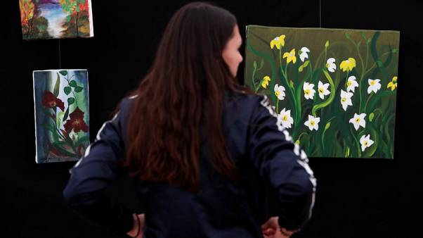 Afghan woman finds peace, hope in painting at Hungary migrant camp