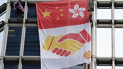 """""""الرجل العنكبوت"""" الفرنسي يتسلق برجا في هونج كونج ويرفع راية مصالحة"""