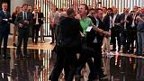 `Climate killer' protester rushes Merkel's stage at Frankfurt car show