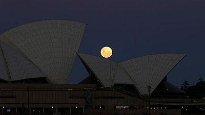 القمر العملاق يظهر وسط سماء صافية فوق دار أوبرا سيدني