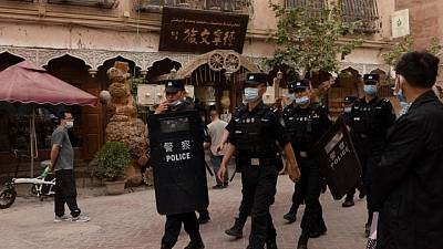 In China's new Xinjiang: patriotic tourism, riot police and minders
