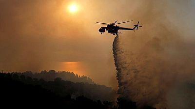 La gente huye de sus casas mientras el fuego arde cerca de zona industrial de Atenas