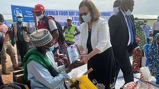 U.S. Embassy Chargé d'Affaires and USAID Country Representative participate in food distribution to commemorate World Food Day
